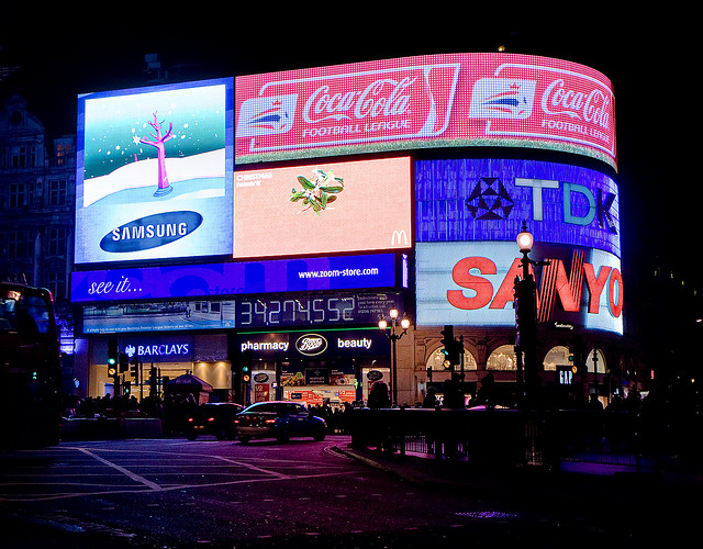 The adverts at Piccadilly Circus lend an eerie glow to the damp road surface.