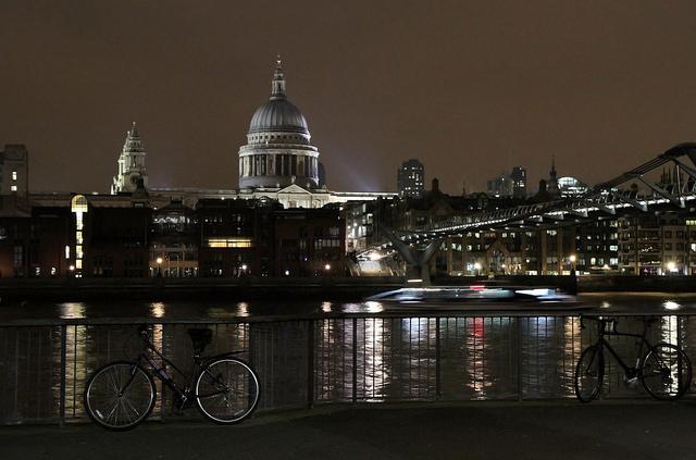 St.Pauls Cathedral illuminated at night with the Millenium Bridge.