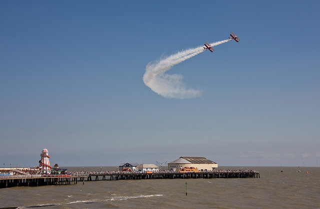 A pair of Stearman biplanes with wing-walkers over Clacton Pier