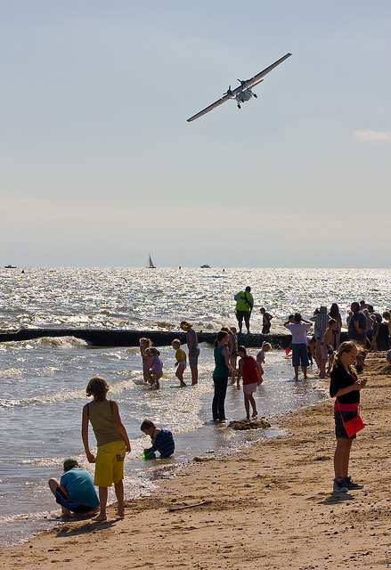 A Catalina displays above the children paddling in the waves
