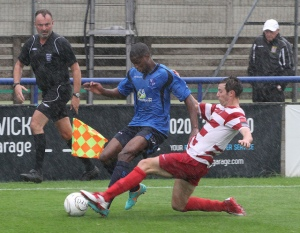 Kingstonian defender takes out Ola in the pouring rain.