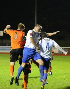 Mark Kirby torture a football as he defends a Wingate corner.