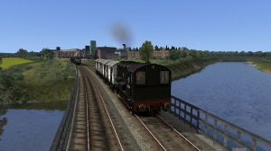 Diesel shunter 13068 crosses the River Nith with a short train of vans from the Carnation Condensed Milk factory visible behind