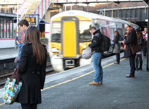 Passengers wait for the 07:44 as the 07:40 fast to Brighton runs through Kentish Town