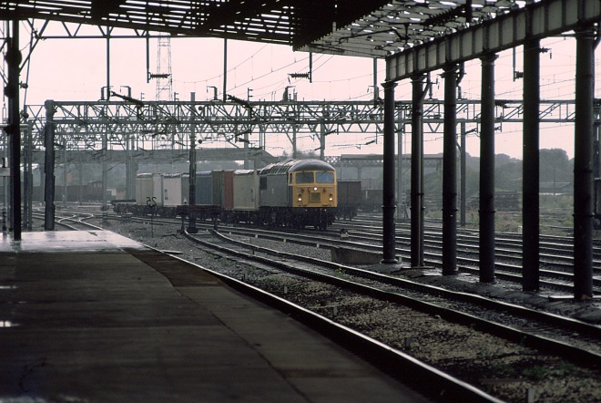An unidentified member of the class hauls a short intermodal service through Rugby.   The majority of the class were withdrawn in 2004 by EWS following the privatisation of British Railways.   Of the 135 strong class 27 have been scrapped.   A few locomotives have returned to service with other operators both abroad and in the UK.   Many remain in store awaiting their fate.