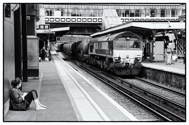 A waiting passenger watches as 66016 runs through Denmark Hill with a freight.