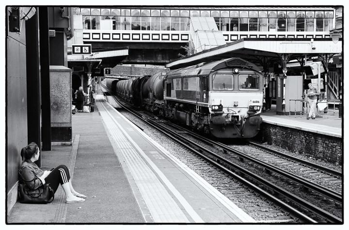 A waiting passenger watches as 66016 runs through Denmark Hill with a freight.